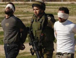 جندي اسراائيلي أثناء اعتقاله شابين فلسطينيين في الضفة