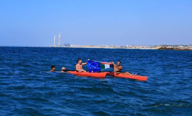 ممثل الاتحاد الأوروبي يرفع العلم الفلسطيني أثناء ممارسته رياضة السباحة في بحر غزة